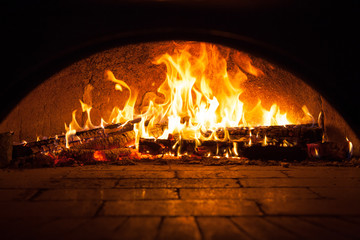 Image of a brick pizza oven with fire