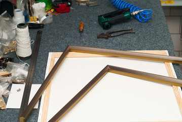 Craftsman working on frame in frame shop. Professional framer hand holding frame angle. Top view. Copy space