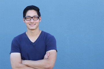 Portrait of a handsome Asian man with glasses crossing his arms