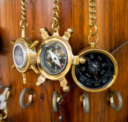Old bronze compasses are hanging on a chain on a wooden wall