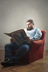 Fat man reading a newspaper