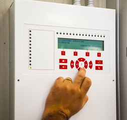 A technician works box panel system fire or smoke alarm