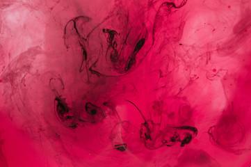 Red, pink, black, white ink in water. Sunshine lighting. Dynamic