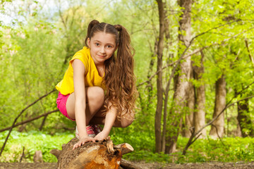 Cute young girl posing on a log in the forest