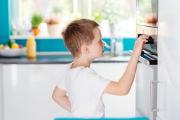 Child Regulating Temperature Of The Oven .