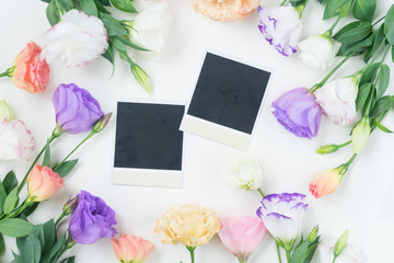 Pink, white and violet eustoma flowers frame with instant photos
