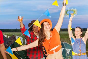 Happy friends having fun at campsite in evening
