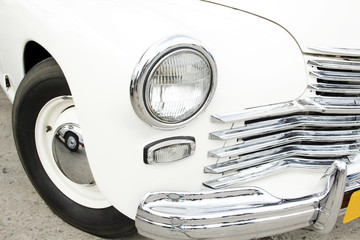 White vintage car on a festival of old cars. Retro car's headlight close up.