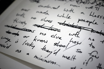"""Lyrics written on paper in black ink close up. Focus on the words """"no clue"""""""