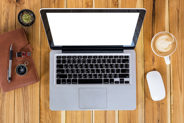 Rustic wooden table with blank screen laptop, pen, eyeglasses and cup of coffee.Top view.Modern office supplies and gadgets.