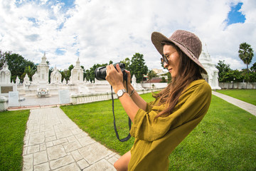 The beautiful girl a blyunetka in a green shirt and a hat in sunglasses, photographs monuments in Thailand, the tourist