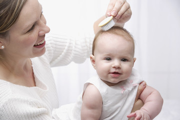 Mother brushing baby's hair