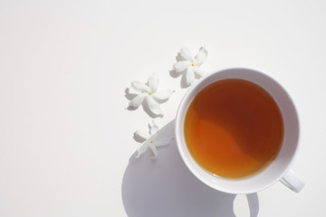 Cup of tea and three white flowers