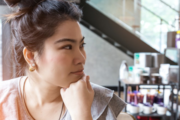 Thinking business woman with free copy space in cafe background