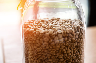 Coffee beans in glass jar on wooden background.