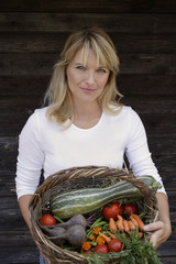 woman with basket of garden vegetables