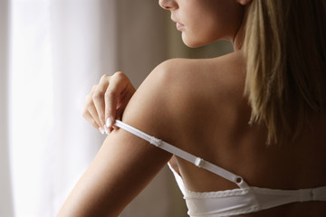 Young woman adjusting bra strap