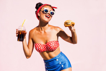 Merry amazing girl eats fast food, drink sodas, eat a burger, a stylish makeup and hairstyle after the barber shop, posing at the camera on a bright pink background, the concept of food crazy emotions