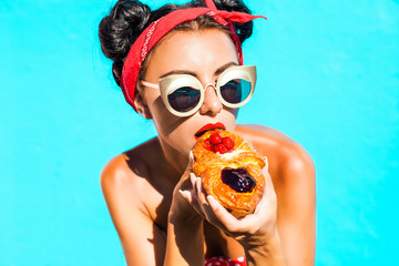 Close-up portrait of a beautiful young sweet girl eating a sweet croissant with a cherry and strawberry, sunglasses, hairstyle with horns, bright makeup, blue wall, tanned skin, red lips