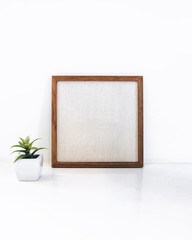 Blank Wooden frame with small Green plant succulent Hipster styl