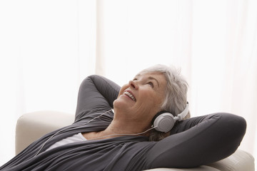 Older woman relaxing listening to music.