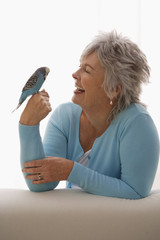 Older woman holding blue bird.