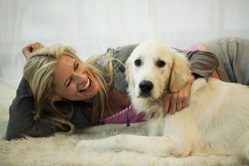 blond woman playing with her dog