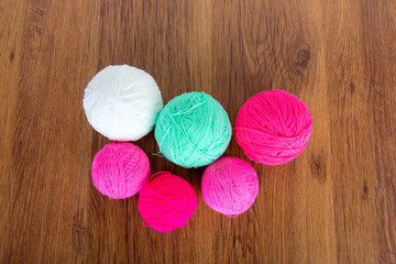 Bright balls of acrylic yarn on a wooden table. Needlework. Knit and Crochet. Fashion trends.