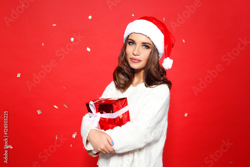 19b17f0bf5 Young beautiful girl stands in a white knitted sweater and santa hat  against a red background behind it shatters And Confetti GOLDEN IN THE  HANDS OF HER RED ...