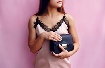 Wall Mural - fashion woman in silk blouse with little black bag in hand
