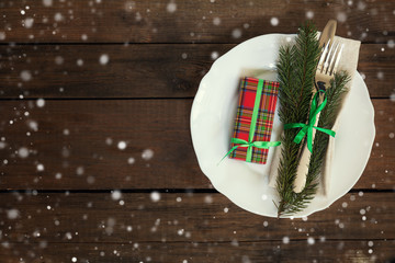 Country style christmas decoration. White empty plate and christmas gift with fir tree, candy, fork and knife tied with a green ribbon on old wooden brown background.