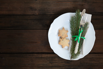 Country style christmas decoration. White empty plate and Christmas cookies with fir tree, candy, fork and knife tied with a green ribbon on old wooden brown background.