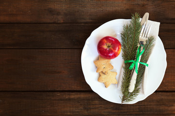 Country style christmas decoration. White empty plate, red apple and Christmas cookies with fir tree, candy, fork and knife tied with a green ribbon on old wooden brown background.