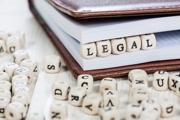 Word LEGAL on white wooden table.