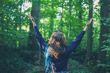 Woman raising her arms in the forest