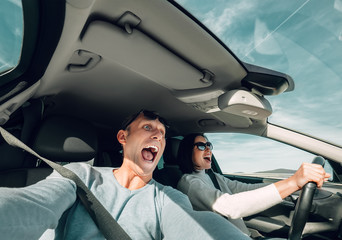 Screaming couple riding in car wide angle view