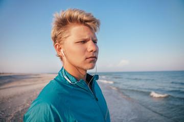 Man with miniature headphones ready to run on the sea beach