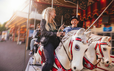 Young couple on amusement park carousel