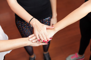 three women holding hands in gym