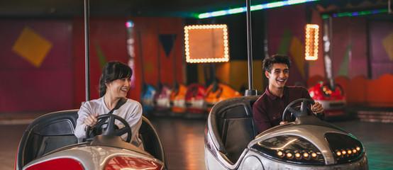 Foto op Aluminium Amusementspark Two young friends riding bumper cars at amusement park