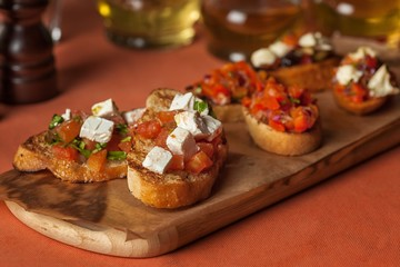 delicious toast with cheese, tomatoes and herbs on a wooden tray