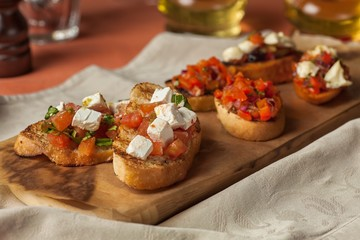 Hot sandwiches with tomatoes and cheese on a wooden tray