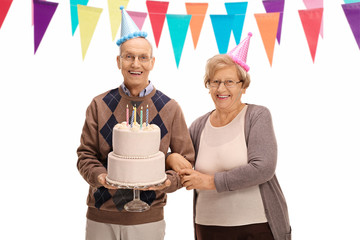 Happy seniors with party hats and a birthday cake