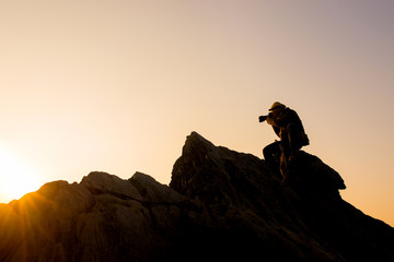 Photographer taking photos on top mountains at morning