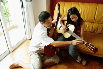 Father teaching daughter how to play the guitar