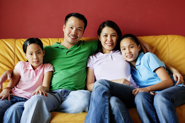 Family of four sitting on sofa, looking at camera