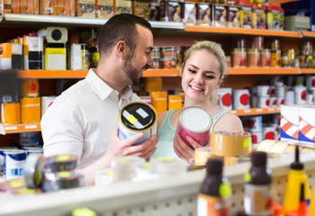 man and woman picking paint tin together in household shop