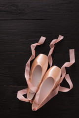 Pink ballet pointe shoes on black wood background