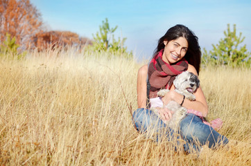 smiling young woman hugging her small havanese dog on a meadow with autumn dry grass
