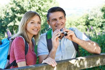 Mature Couple Hiking In Countryside Looking Through Binoculars